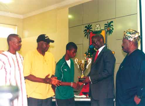 Captain of 36 Lion, Adeola Odamo presents the 2009 Chicago Cup to Governor Babatunde Raji Fashola, while the State's Sports Commissioner, Ademola Adeniji-Adele (right), SA to the governor on Grassroots Sports, Prince 'Wale Oladunjoye (2nd left) and CEO of the club, Gafar Liameed look on.