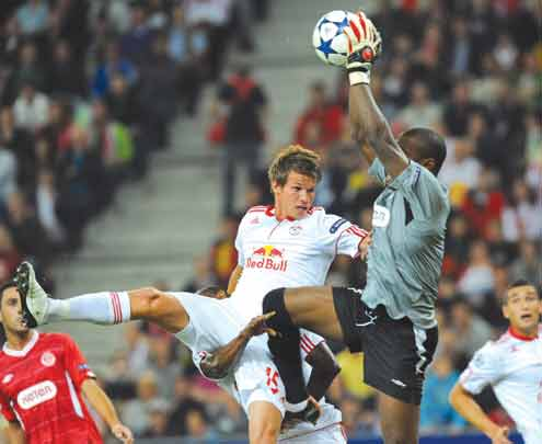 Hapoel Tel Aviv's Goalkeeper, Nigerian Vincent Enyeama (right) saves the ball amidst struggle with Red Bull Salzburg's Franz Schiemer during their UEFA Champions League Play-off first-leg round football match in Salzburg on 18 August, 2010. PHOTO:  AFP.