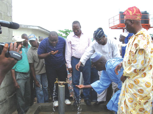 Commissioner for Rural Development, Prince Lanre Balogun (middle) and others drinking from a water project.