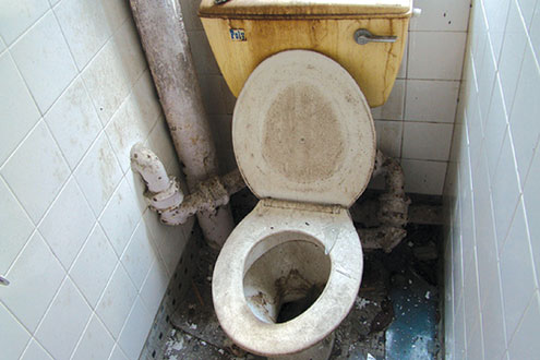 One of the dirty toilets in an eatery.