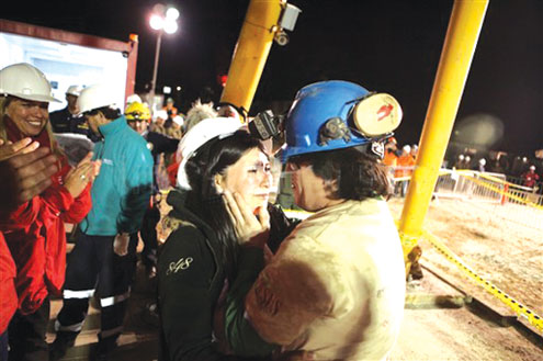 Chilean miner Osman Araya (R) is welcomed by his wife Angelica as he comes out of the Fenix capsule after being brought to the surface this morning following a 10-week ordeal in the collapsed San Jose mine, near Copiapo, 800 km north of Santiago, Chile. Araya was the sixth from the 33 trapped miners to be lifted from underground. AFP photos.
