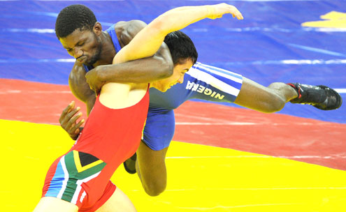 BRONZE EFFORT…Romeo Joseph of Nigeria (blue) wrestles with Marius Loot of South Africa on the way to winning the bronze medal in the 60kg category of the Greco-Roman Wrestling at the 2010 Commonwealth Games in New Delhi yesterday. PHOTO: AFP.