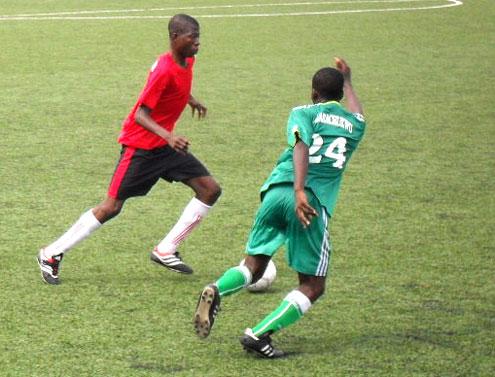 Ali Lukman of Ifako Ijaiye (left) fights for the ball with Amara Chukwu Uche of Odi-Olowo during their Lagos Junior League match.