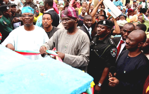 Fashola (left) cutting the tape for a rural electrification project with the Commissioner for Rural Development, Prince Lanre Balogun.