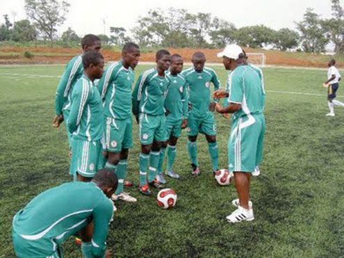 Flying Eagles listen to Coach John Obuh during a training session.