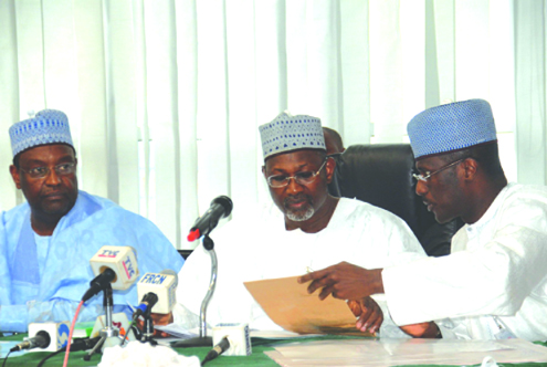 INEC Chairman, Prof. Attahiru Jega (middle), assisted by his PA Abdulahi Usman (right), while Alhaji Nuhu Yakubu, a Commissioner, looks on during the announcements of the presidential election report in Abuja yesterday. Photo: Femi Ipaye.