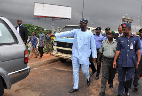 Lagos State Governor, Mr. Babatunde Fashola SAN (left), pointing at one of the vehicles illegally displayed on the road for sale during his visitation to the Airport Road, Ikeja, along with other military service commanders on Thursday, June 9, 2011. With him are: Commander 9 Brigade Ikeja, Brigadier General Sanusi Nasiru Muazu (middle) and Airforce Commander 435 BSG Ikeja, Group Captain Ayo Saad Abdulsalam (right).