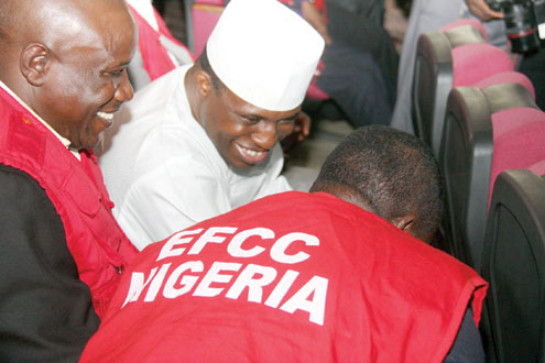 Dimeji Bankole sandwiched by EFCC officials in court. PHOTO: FEMI IPAYE.