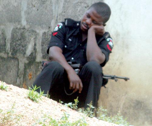 A Nigerian policeman sleeps on duty during the burial of the slain police DCO in Badagry at the weekend. PHOTO: KOLA ALIYU.