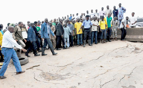 Lagos State Governor, Mr. Babatunde Fashola (SAN) with the Permanent Secretary (Office of Drainage), Ministry of  The Environment, Engr. Muyideen Akinsanya (left), Commissioner for The Environment, Mr. Tunji Bello (2nd left), inspecting the road that caved-in at Obadeyi Bus Stop Abeokuta Expressway, Lagos, yesterday.