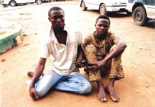 Sodiq Olabisi (left) and Sunday Adegbola holding a pistol.