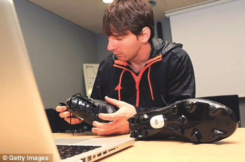 Messi taking a look at the 'brain boot' . PHOTOS: Daily Mail.