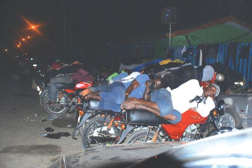 Mobile Beds: Homeless Okada Riders sleep on thier bikes infront of Dodan Barracks, Obalende Lagos, Southwest Nigeria at 3am this morning. Photo: ABEEB OGUNBADEJO.
