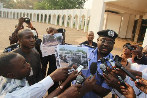 SECURITY & SECURITY1: Inspector General of Police, Mr. Hafiz Ringim displaying photographs of the damaged properties at the Kano State Government House after a Security Meeting at the State House, Abuja.  10/01/2012