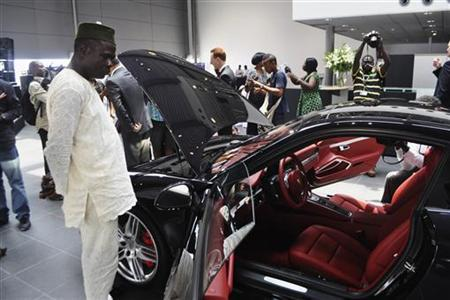 A Nigerian man looks at a vehicle by German carmaker Porsche in Lagos