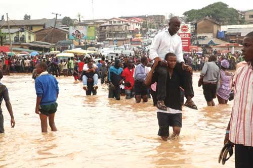 Street boys ferry communters across a flooded bridge at Yakoyo area of Ogun State this morning.  PHOTO: EMMANUEL OSODI.