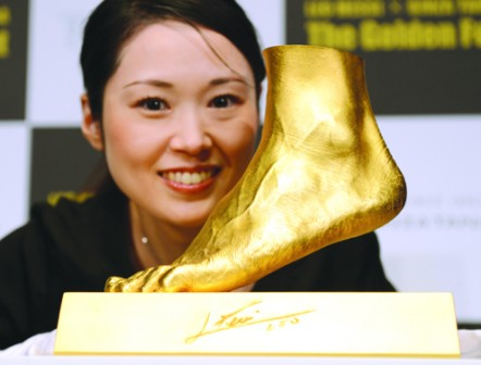 •An employee of Ginza Tanaka poses beside the golden replica of  Lionel Messi of Argentina's left foot during its press preview in Tokyo early today.  The 25-kilogramme golden foot was created by Tokyo-based jewelry retailer, Ginza Tanaka, to commemorate Messi's record-breaking Ballon d'Or for four consecutive years and the world-record 91 goals he scored in a calendar year.    PHOTO: AFP.