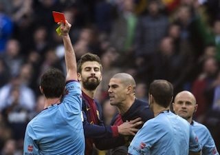 """Barcelona's goalkeeper Victor Valdes (C) argues with referee Perez Lasa (R) showing him a red card at the end of the """"El clasico"""" AFP photo"""