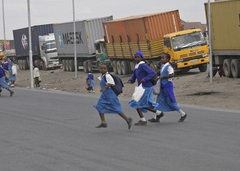 school children walk across a road in Nigeria