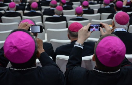 Bishops take pictures of Pope Francis with mobile phones at the Archbishop's Palace in Rio de Janeiro, Brazil
