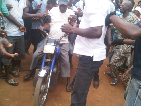 The alleged gay, Sadiq, being whisked away from the scene.
