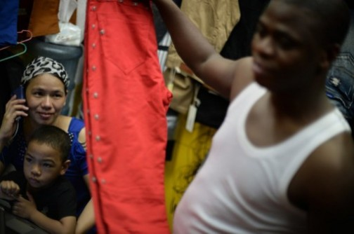 Lamine Ibrahim (R) from Guinea smiles as his Chinese wife Maryam Barry (L) looks on with their son at their shop inside a clothing wholesale market in Guangzhou.