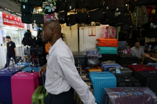 39-year-old trader Ali Diallo from Guinea (front), who sells Chinese electronics to retailers across Africa, walks through Chungking Mansions --  a bustling labyrinth known for budget hotels and no-frills restaurants -- in Hong Kong.