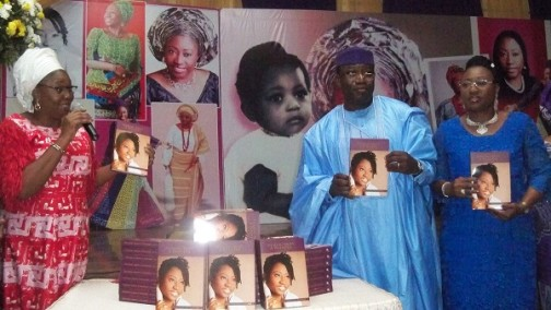 Dame Abimbola Fashola unveils one of the books. Governor Fayemi and his wife stand on the right