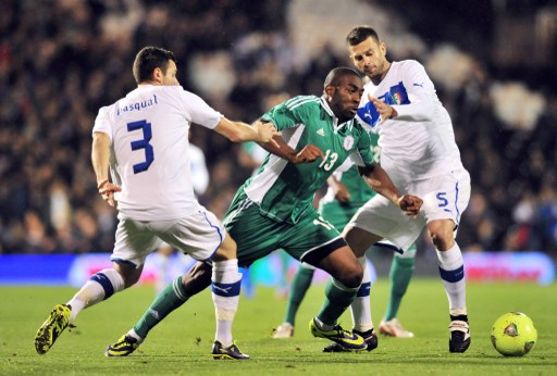 Bright Dike challenged by two Italian defenders