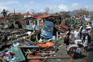 Residents walk past debris and destroyed houses along a road in Tacloban City, AFP
