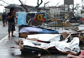 A woman mourns in front of her husband's dead body in a street of Tacloban,