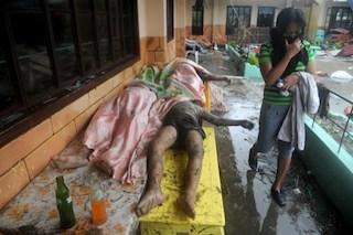A woman walks past dead bodies inside the Fisherman's Village Elemantary School in Tacloban. AFP