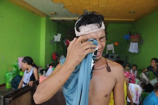 A resident who survived Typhoon Haiyan cries inside a stadium used as an evacuation centre in Tacloban,