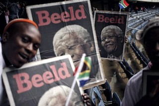 South Africans sing while holding a cover of the Afrikaans daily Beeld inside Orlando Stadium in Soweto,
