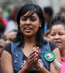 A woman applauds as she watches the retransmission of the memorial service for late former South African president Nelson Mandela, on a giant screen in front of the city hall in Durban on 10 december