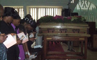 Iyetade's coffin and the family members in the front