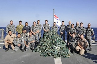 Australia's naval officers pose with hashish piled up on the ship's flight deck