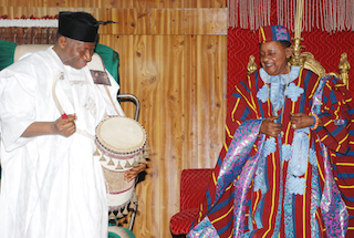 Trying his hands on the talking drum in Oyo