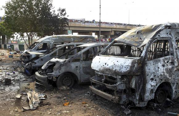 Burnt and damaged vehicles are seen at the scene of the bomb blast explosion in Abuja
