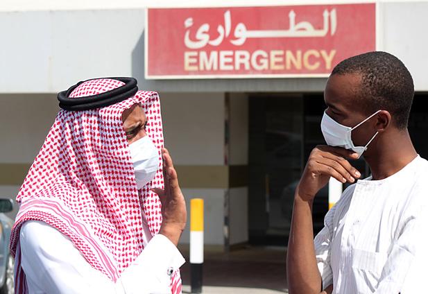 Men wearing surgical masks as a precautionary measure against the novel coronavirus, speak at a hospital in Khobar city in Dammam