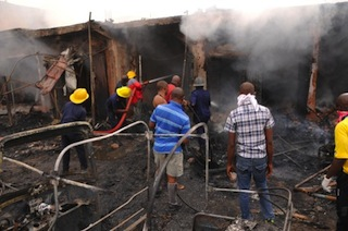 Firefighters extinguish a fire at the scene of a bomb blast at Terminus market in the central city of Jos AFP