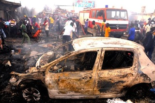 Firefighters and rescuers extinguish a fire at the scene of a bomb blast at Terminus market in the central city of Jos on May 20, 2014.
