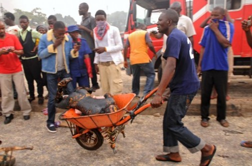 Jos bombing: a rescuer carries away the charred remains of a victim