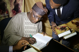 The Author, Olusegun Obasanjo authograph one the book at the event.