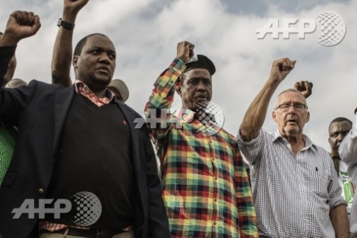 Edgar Lungu, middle and Guy Scott, right, sing national anthem