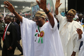 President Goodluck Jonathan acknowledges cheers from supporters, with him is PDP Chairman , Adamu Mu'azu