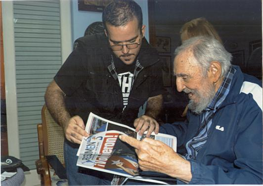 Former Cuban President Fidel Castro and President of Cuba's University Students Federation Randy Perdomo look at a newspaper during a meeting in Havana