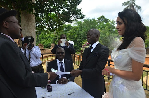 The officiating minister hands marriage certificate to Governor Oshiomhole