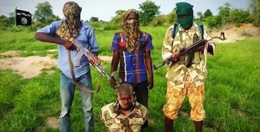 A Nigerian soldier is made to kneel in front of three militants after he was captured by Boko Haram