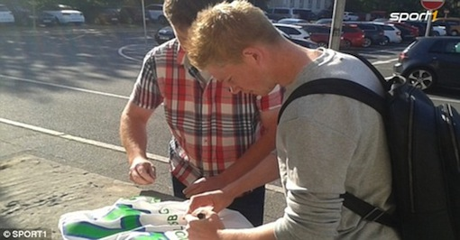 At the airport, Kevin De Bruyne signs a jersey for a Wolfsburg fan